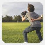 Un niño que lleva un guante de béisbol espera a su pegatina cuadrada