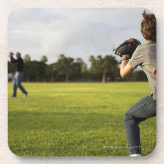 Un niño que lleva un guante de béisbol espera a su posavasos de bebidas