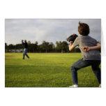 Un niño que lleva un guante de béisbol espera a su tarjeta de felicitación