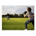 Un niño que lleva un guante de béisbol espera a su tarjetas postales