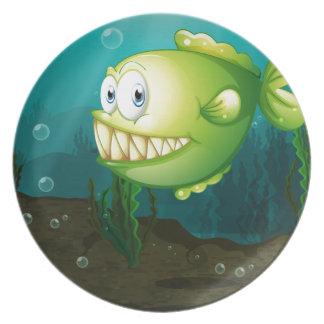Un pescado verde con los colmillos grandes debajo plato para fiesta