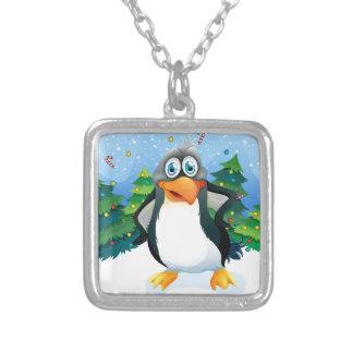 Un pingüino cerca de los árboles de navidad colgante cuadrado