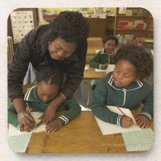 Un profesor ayuda a alumnos jovenes en ella posavaso