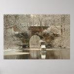 Un puente de piedra arqueado en invierno posters