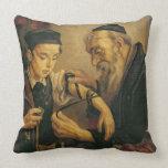 Un rabino que ata los Phylacteries al brazo de un  Almohada