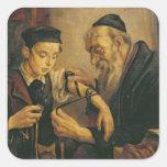 Un rabino que ata los Phylacteries al brazo de un Pegatina Cuadradas