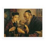 Un rabino que ata los Phylacteries al brazo de un Postal