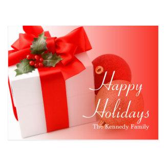 Un regalo del navidad con acebo decorativo tarjetas postales