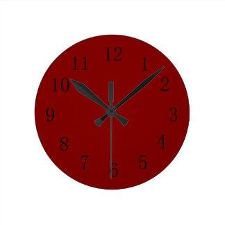 Un reloj de pared rojo marrón más oscuro de la