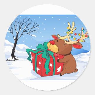 Un reno que sostiene un regalo pegatina redonda