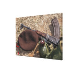 Un rifle, militar cubre y cantina lienzo envuelto para galerias