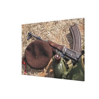 Un rifle, militar cubre y cantina lona envuelta para galerías