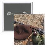 Un rifle, militar cubre y cantina pins