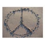 Un signo de la paz dibujado en la arena postal