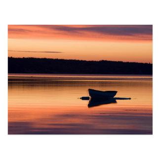 Un skiff en la salida del sol en el alcance de tarjeta postal