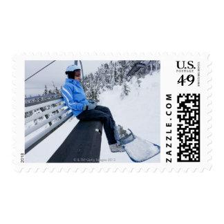 Un snowboarder de sexo femenino monta la elevación sellos
