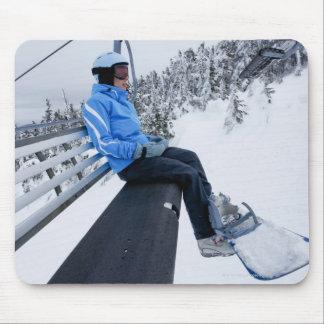 Un snowboarder de sexo femenino monta la elevación tapetes de ratón