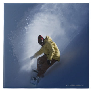 Un snowboarder de sexo masculino coge la luz pasad azulejo cuadrado grande