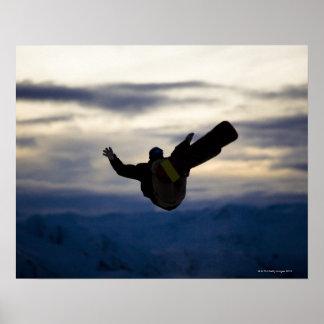 Un snowboarder de sexo masculino hace un salto mor póster