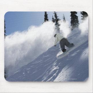 Un snowboarder de sexo masculino que rasga el polv alfombrilla de ratones