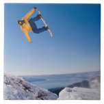 Un snowboarder hace girar apagado un salto en la A Azulejo Cuadrado Grande