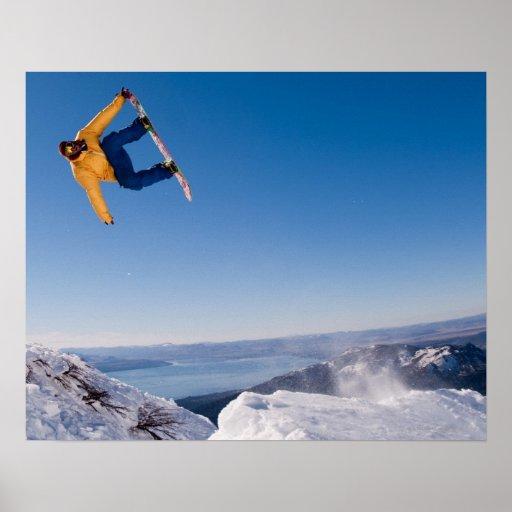 Un snowboarder hace girar apagado un salto en la A Póster