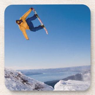 Un snowboarder hace girar apagado un salto en la posavasos