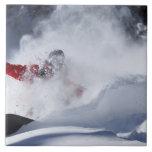 Un snowboarder rasga vueltas untracked del polvo a azulejo cuadrado grande