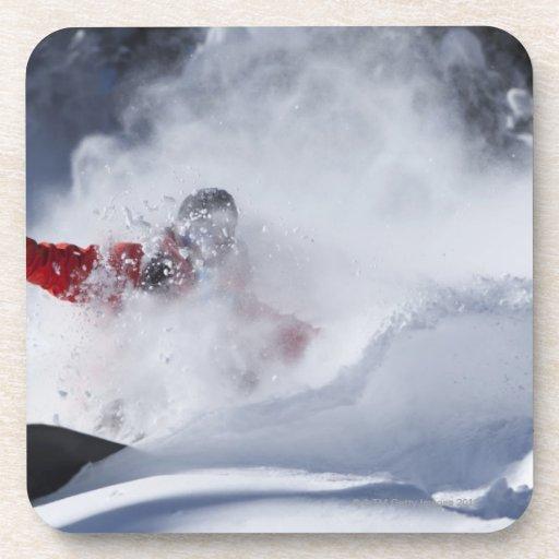 Un snowboarder rasga vueltas untracked del polvo a posavasos