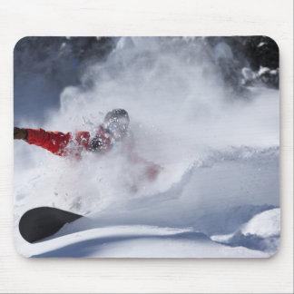 Un snowboarder rasga vueltas untracked del polvo a tapete de raton