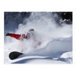Un snowboarder rasga vueltas untracked del polvo a tarjetas postales