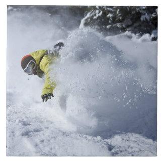 Un snowboarder rasga vueltas untracked del polvo e azulejo cuadrado grande