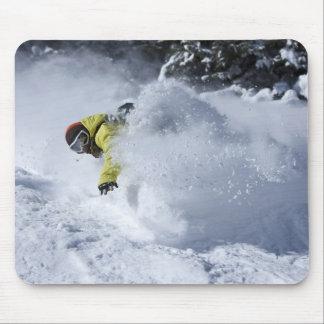 Un snowboarder rasga vueltas untracked del polvo e alfombrilla de ratones