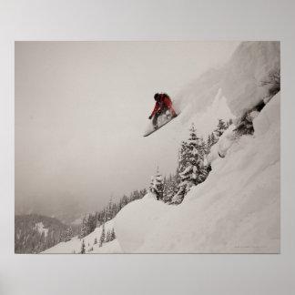 Un snowboarder salta de un acantilado en polvo ade impresiones