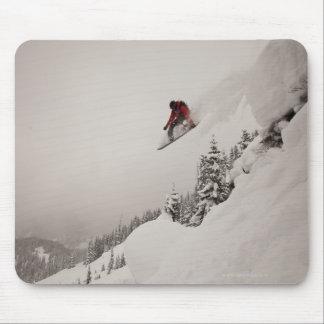 Un snowboarder salta de un acantilado en polvo ade tapete de raton