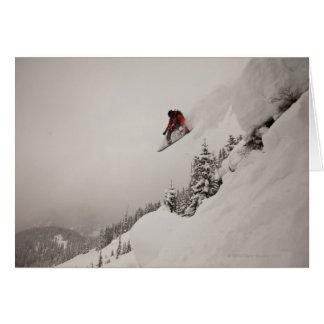 Un snowboarder salta de un acantilado en polvo ade tarjeta de felicitación
