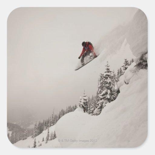 Un snowboarder salta de un acantilado en polvo calcomanía cuadradas personalizada