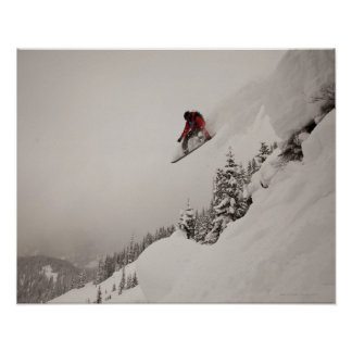 Un snowboarder salta de un acantilado en polvo póster