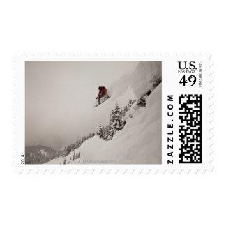 Un snowboarder salta de un acantilado en polvo envio