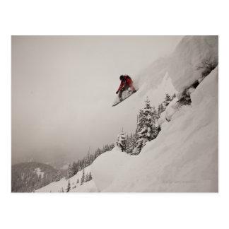 Un snowboarder salta de un acantilado en polvo tarjeta postal