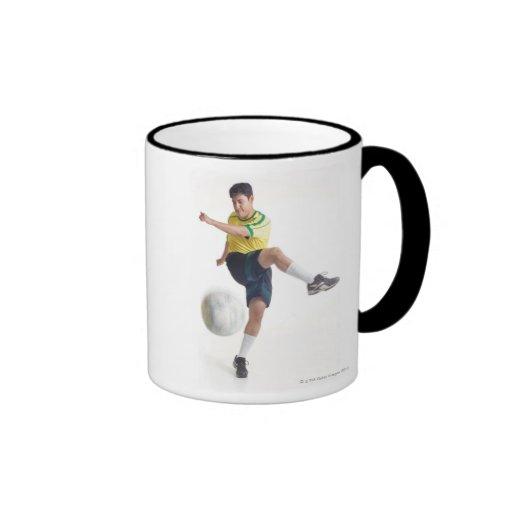 un varón latino joven lleva un jersey de fútbol am taza