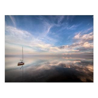 Un velero solitario en las aguas tranquilas de postales