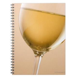 Un vidrio de vino blanco libro de apuntes con espiral
