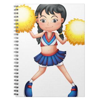 Una animadora en su uniforme con los pompoms libro de apuntes