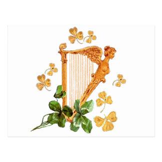 Una arpa irlandesa de oro rodeada por los tréboles tarjeta postal