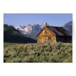 Una cabaña de madera y las montañas del diente de  tarjetas