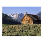 Una cabaña de madera y las montañas del diente de postales
