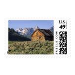 Una cabaña de madera y las montañas del diente de timbres postales