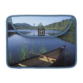 Una canoa descansa sobre la orilla de poca charca  funda macbook pro