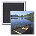 Una canoa descansa sobre la orilla de poca charca  iman de frigorífico
